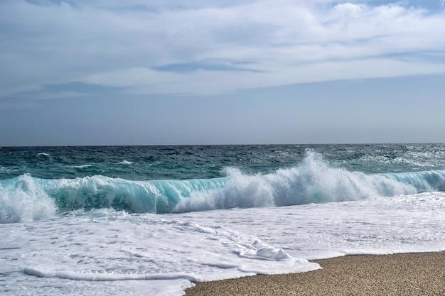 Mooi landschap van overzeese golven die onder een bewolkte hemel bespatten