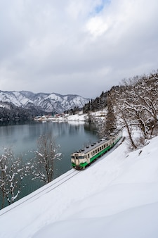 Mooi landschap van tadami-lijntrein over tadami-rivier in de winter in fukushima, japan