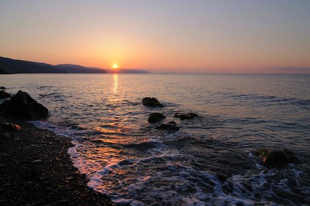 Mooi landschap, zonsondergang aan zee, zon komt op van achter de bergen