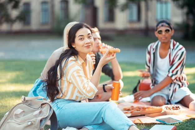 Mooi langharig meisje glimlachend terwijl het eten van pizza met haar groepsgenoten