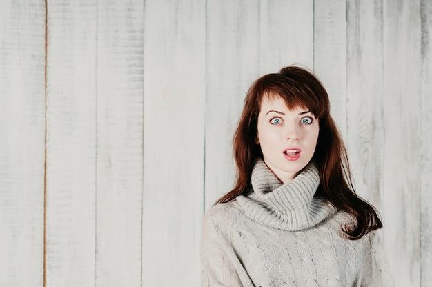 Mooi langharig meisje in een grijze trui, verrast grote ogen, open mond