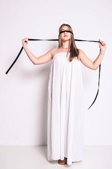 Mooi langharig meisje in een lange geblinddoekte jurk