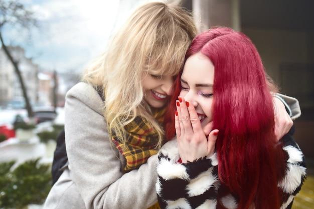 Mooi lesbisch koppel. knuffel van twee vrouwen. blond en rood haar modellen. lopen op straat