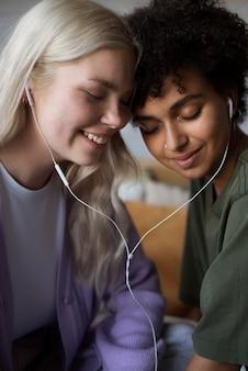 Mooi lesbisch koppel luisteren naar muziek op oortelefoons
