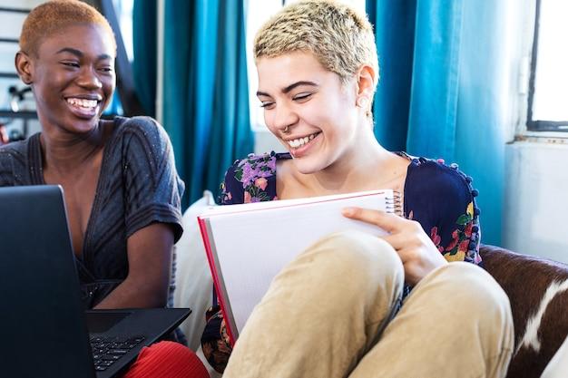 Mooi lesbisch koppel met een laptop die thuis op de bank rust