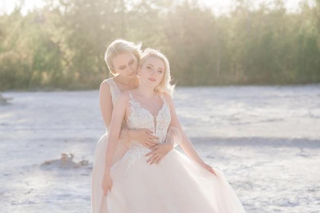 Mooi lesbisch koppel wandelen op zand langs de oever van de rivier op hun trouwdag