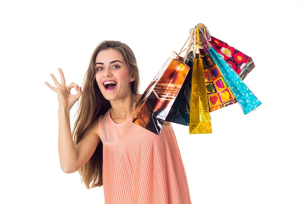 Mooi leuk meisje geniet van nieuwe aankopen en houdt pakketten in haar hand