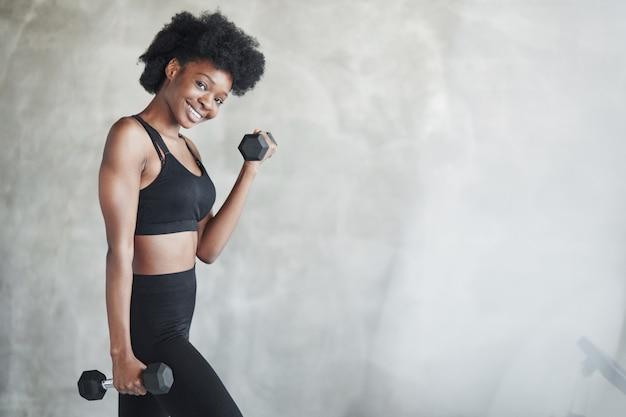 Mooi lichaam. studio shot van jonge vrouw die voor grijze achtergrond staat met halters in handen