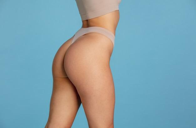 Mooi lichaam van jonge blanke vrouw geïsoleerd op blauwe achtergrond.