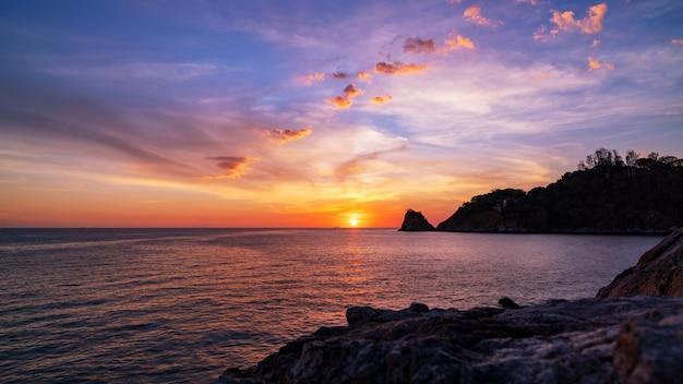 Mooi licht van aard dramatisch hemelzeegezicht met rots op de voorgrond op de achtergrond van het zonsonderganglandschap.