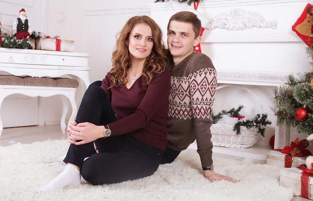 Mooi liefdepaar op tapijt. vrouw en man vieren kerstmis