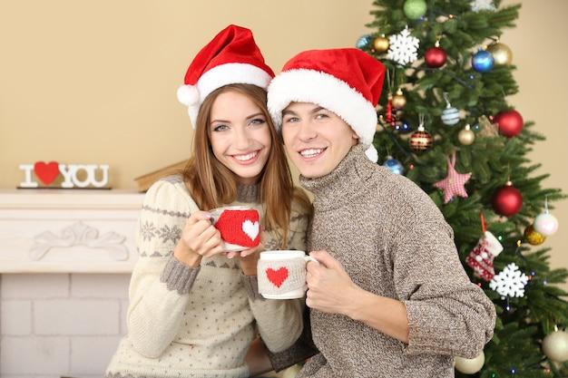Mooi liefdespaar zittend met mokken voor open haard in de buurt van kerstboom. vrouw en man vieren kerstmis