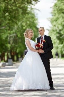 Mooi liefhebbend bruidspaar registreert een huwelijk en loopt langs de prachtige promenade. geluk en liefde in de ogen van mannen en vrouwen. ,