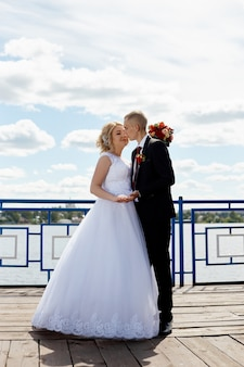 Mooi liefhebbend bruidspaar registreert een huwelijk en loopt langs de prachtige promenade
