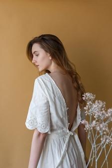 Mooi mager jong meisje met lang haar in witte jurk met naakte rug poseren op beige achtergrond