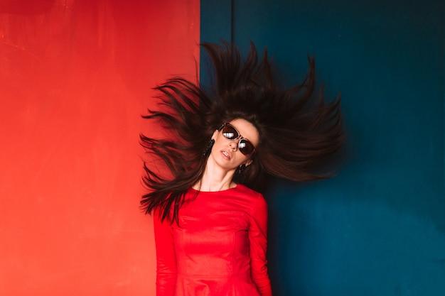 Mooi maniermeisje met lang haar in zonnebril en het rode elegante kleding stellen op blauwe rode muur. stijlvolle brunette babe met vliegend haar. professioneel kapselconcept