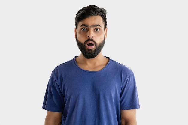 Mooi mannelijk geïsoleerd portret. jonge emotionele hindoe man in blauw shirt. gelaatsuitdrukking, menselijke emoties. geschokt en verbaasd.