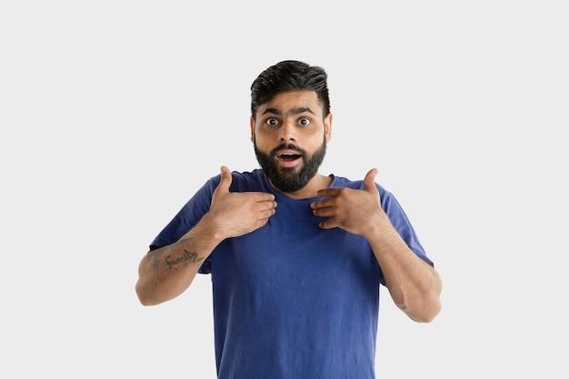 Mooi mannelijk geïsoleerd portret. jonge emotionele hindoe man in blauw shirt. verbaasd, geschokt, krankzinnig blij.
