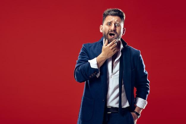 Mooi mannelijk half-lengteportret dat op trendy rode studioachtergrond wordt geïsoleerd. jonge emotioneel verraste, gefrustreerde en verbijsterde man.