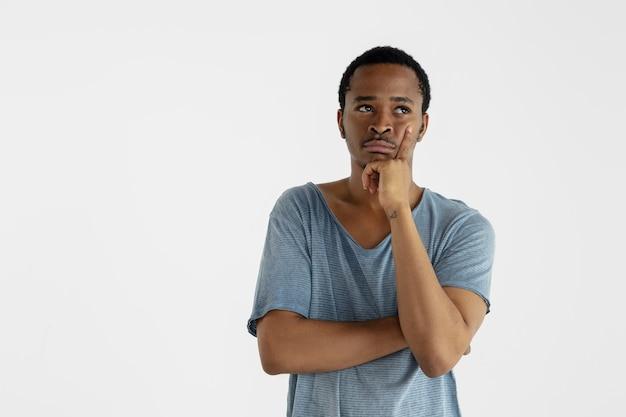 Mooi mannelijk half-lengteportret dat op witte muur wordt geïsoleerd. jonge emotionele afro-amerikaanse man in blauw shirt. gelaatsuitdrukking, menselijke emoties, advertentieconcept. nadenken, omhoog kijken.