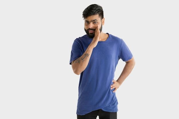 Mooi mannelijk half-lengteportret dat op witte muur wordt geïsoleerd. jonge emotionele hindoe-man in blauw shirt. gelaatsuitdrukking, menselijke emoties, reclameconcept. glimlachen, een geheim fluisteren.