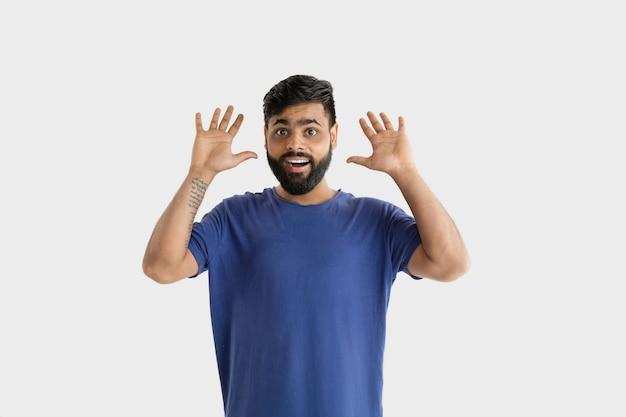 Mooi mannelijk half-lengteportret dat op witte studioachtergrond wordt geïsoleerd. jonge emotionele hindoe man in blauw shirt. gelaatsuitdrukking, menselijke emoties, advertentieconcept. verbaasd, geschokt, krankzinnig blij.