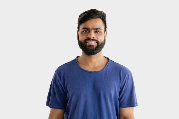 Mooi mannelijk half-lengteportret dat op witte studioachtergrond wordt geïsoleerd. jonge emotionele hindoe man in blauw shirt. gelaatsuitdrukking, menselijke emoties, reclameconcept. staan en glimlachen.