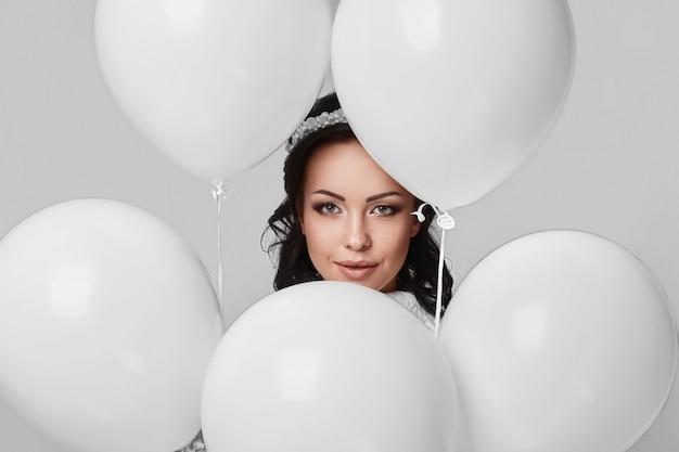 Mooi mannequinmeisje met witte ballons