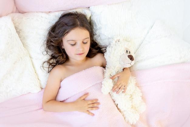 Mooi meisje 5-6 jaar oud slapen in een bed met een teddybeer