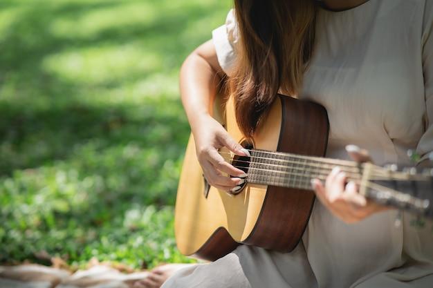 Mooi meisje akoestische gitaar spelen in de tuin