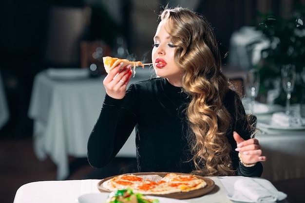 Mooi meisje alleen pizza eten in een restaurant.