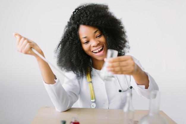 Mooi meisje arts in een witte jas met een stethoscoop. zitten aan een tafel en monster analyseren in laboratorium. laboratoriumassistent analyseren van een monster.