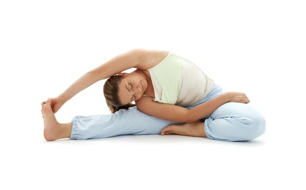 Mooi meisje ashtanga yoga beoefenen over wit