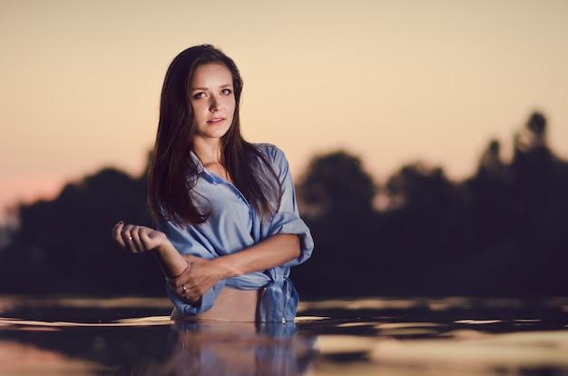 Mooi meisje baden in het meer in een warme zomeravond
