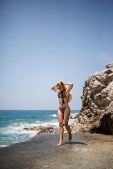 Mooi meisje blond in zwembroek poseren op het strand op de rotsen
