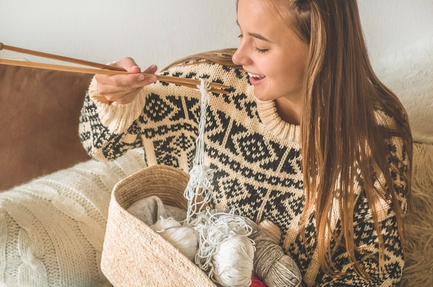 Mooi meisje breit een warme trui op het bed. breien als hobby. accessoires voor breien.