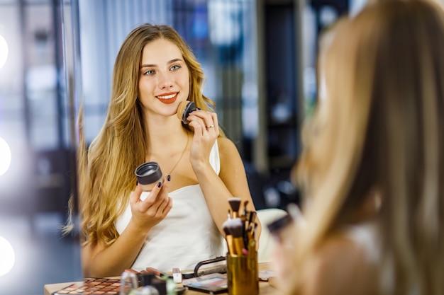 Mooi meisje brengt poeder op het gezicht aan bij het maken van make-up.