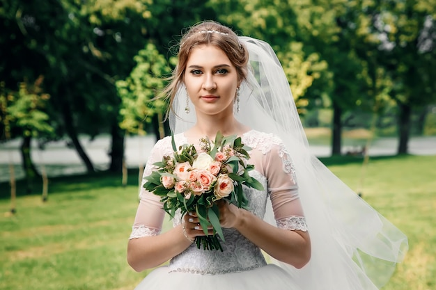 Mooi meisje, bruid in een witte trouwjurk op een achtergrond van groene natuur. bruiloft, familiecreatie.