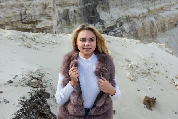 Mooi meisje brunette in t-shirt en korte broek ocer bontjas poseren op lege zand rotsen