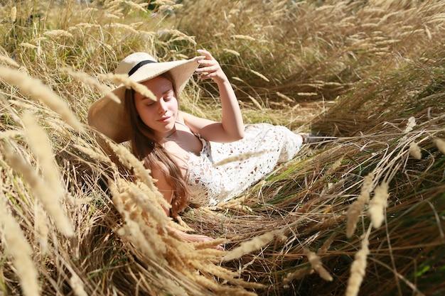 Mooi meisje buiten ontspannen in goudgele tarwe. moderne boho-stijl.