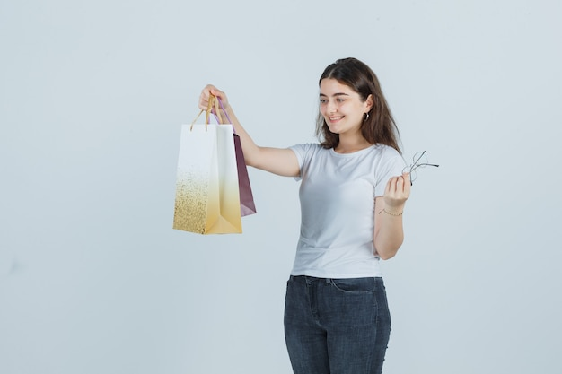 Mooi meisje cadeauzakjes in t-shirt, spijkerbroek kijken en op zoek gelukkig. vooraanzicht.