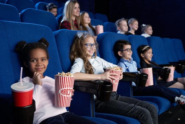 Mooi meisje camera kijken tijdens het kijken naar film in de bioscoop