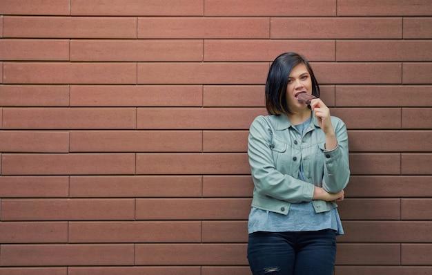 Mooi meisje chocolade-ijs eten op een stokje. vrouw op een bakstenen muur op straat
