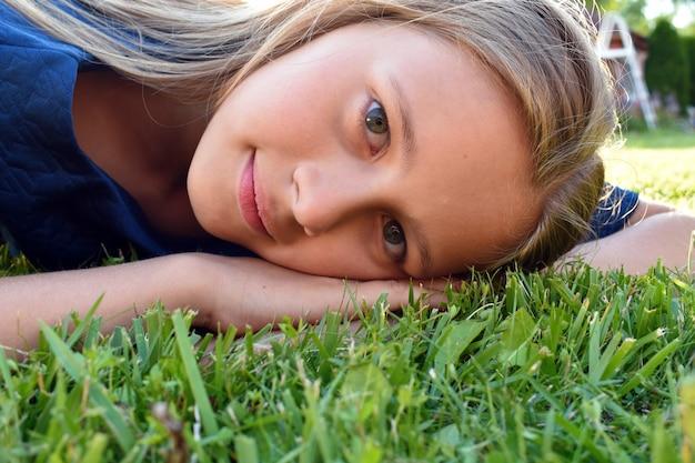 Mooi meisje close-up op groen gras in de zomer.