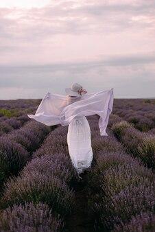 Mooi meisje dansen op lavendelveld, draait op paarse bloem weide