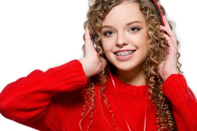 Mooi meisje dat aan muziek in rode hoofdtelefoons luistert. isoleren. portret van een meisje met orthodontisch apparaat.