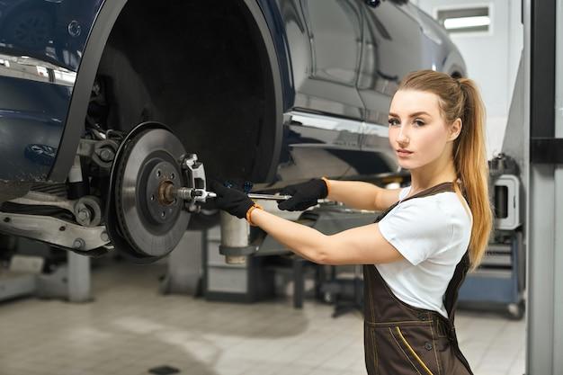 Mooi meisje dat als werktuigkundige in autoservice werkt, die auto bevestigt.