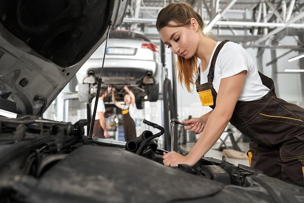 Mooi meisje dat als werktuigkundige in autoservice werkt.