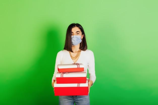 Mooi meisje dat beschermend gezichtsmasker draagt dat de dozen van giften houdt die over groene achtergrond worden geïsoleerd