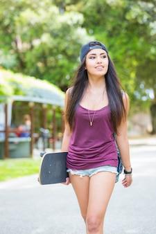Mooi meisje dat bij park loopt dat een skateboard houdt.